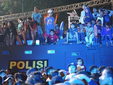 Warga menyaksikan hiburan di atas mobil barracuda pada malam puncak peringatan HUT DKI Jakarta ke-492 di Bundaran HI Jakarta, Sabtu, (22/6/2019). Peringatan HUT Jakarta yang dibuka Gubernur DKI Jakarta Anies Baswedan dikemas dalam konsep ekonomi kreatif dan seni. (Liputan6.com/Immanuel Antonius)