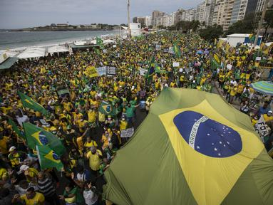 Pendukung Presiden Brasil Jair Bolsonaro membawa bendera nasional di sepanjang Pantai Copacabana pada Hari Kemerdekaan di Rio de Janeiro, Selasa (7/9/2021). Ribuan orang tersebut terbagi dalam dua kubu yaitu pendudukung serta penentang Presiden Brasil Jair Bolsonaro. (AP Photo/Bruna Prado)