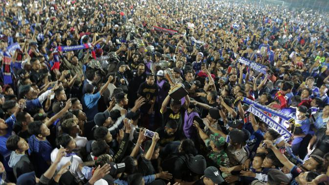 Lautan manusia memenuhi area lapangan Stadion Kanjuruhan, Malang, pada Jumat (12/4/2019) malam. Para pemain Arema FC dikerubuti Aremania yang bersuka cita tim kesangannya juara Piala Presiden 2019. (Bola.com/Yoppie Renato)