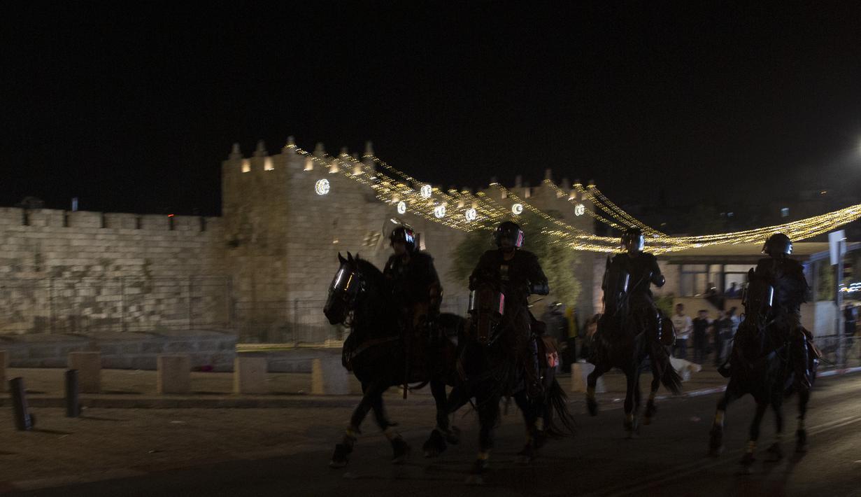 Petugas polisi Israel dengan menunggang kuda mengejar pemuda Palestina di dekat Gerbang Damaskus ke Kota Tua Yerusalem, selama bulan suci Ramadhan, Senin (19/4/2021). Polisi Israel bentrok dengan pengunjuk rasa Palestina, mengeluarkan meriam air dan kuda untuk membubarkan kerumunan. (AP Photo/Maya A