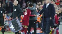 Pelatih Liverpool, Jurgen Klopp memeluk gelandang Takumi Minamino usai ditarik keluar pada pertandingan melawan Everton di babak ketiga Piala FA di Anfield, Minggu (5/1/2020). Minamino bermain selama 70 menit, lalu digantikan Alex Oxlade-Chamberlain. (AP Photo/Jon Super)