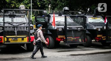 Petugas kepolisian melintas di depan mobil taktis yang disiapkan untuk pengamanan terkait pemeriksaan Rizieq Shihab di Polda Metro Jaya, Jakarta, Senin (7/12/2020). Polda Metro Jaya mengagendakan pemeriksaan terhadap Habib Rizieq Shihab (HRS) hari ini. (Liputan6.com/Faizal Fanani)