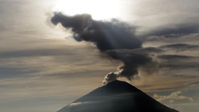 Embusan asap keluar dari kawah Gunung Agung ketika matahari terbit (sunrise) yang terlihat dari Kintamani, Bali, Rabu (13/12). BNPB menegaskan bahwa kondisi Pulau Bali aman bagi wisatawan meski Gunung Agung berstatus siaga. (AP Photo/Firdia Lisnawati)