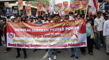 Massa yang tergabung dalam aliansi mahasiswa dan pemuda relawan cinta NKRI membawa spanduk saat unjuk rasa di depan Gedung Bawaslu, Jakarta, Jumat (17/5). Dalam aksinya mereka menolak Gerakan People Power karena syarat dengan kepentingan politik inkonstitusional. (Liputan6.com/Faizal Fanani)