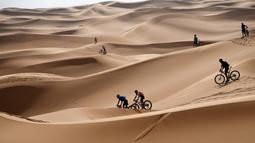 Para pebalap mengendarai sepeda melintasi sepanjang bukit pasir pada etape 1 edisi ke 14 balap sepeda gunung Titan Gurun 2019 di sekitar Kota Merzouga, Maroko, Minggu (28/4/2019). Trek Titan Gurun 2019 sepanjang 640 km menghubungkan antara Merzouga dan Maadid. (Franck Fife / AFP)