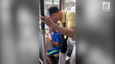 Seorang pria memaksa seorang bocah laki-laki untuk memberikan kursi kepadanya. Insiden terjadi di dalam sebuah bus di kota Chengdu, China.