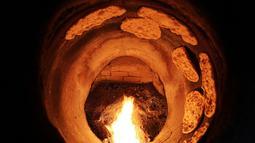 Proses pemanggangan roti Iran atau taftoon dalam oven tradisional di sebuah toko di Kuwait City, Kuwait, 27 Juni 2019. Taftoon telah menjadi makanan pokok untuk sarapan, makan siang, dan selalu menghiasi meja makan orang Kuwait selama beberapa dekade. (YASSER AL-ZAYYAT/AFP)