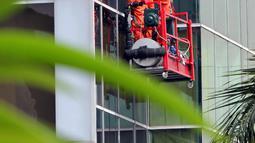 Pekerja membersihkan bagian luar gedung di kawasan Kuningan, Jakarta, Selasa (3/6). Menaker Hanif Dhakiri mengatakan angka kecelakaan kerja secara nasional masih sangat tinggi yaitu 103.000 per tahunnya. (Liputan6.com/Helmi Afandi)
