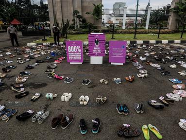 Ratusan sepatu diletakan saat aksi diam 500 Langkah Awal Sahkan Rancangan Undang-Undang Penghapusan Kekerasan Seksual (RUU PKS) di depan gedung DPR, Jakarta, Rabu (25/11/2020). (Liputan6.com/Johan Tallo)