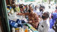 Menteri Koperasi dan Usaha Kecil dan Menengah (UKM) Teten Masduki meninjau pedagang Pasar Cempaka Putih, Jakarta, Kamis (11/6/2020). Kunjungan Menkop UKM tersebut untuk mengecek kondisi perdagangan pasar saat PSBB Transisi. (Liputan6.com/Faizal Fanani)