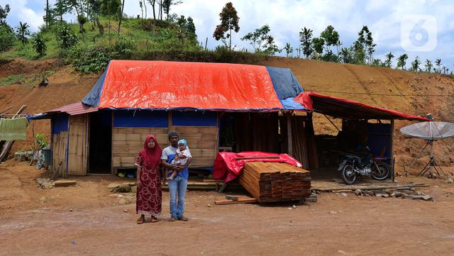 Marjuk (41) bersama keluarga berpose di Kampung Cigobang, Lebak, Banten, Sabtu (20/3/2021). Pascabencana banjir bandang dan longsor yang terjadi di Kampung Cigobang pada 1 Januari 2020 lalu mengakibatkan sekitar 154 kepala keluarga (KK) meninggalkan kampung tersebut. (Liputan6.com/Herman Zakharia)