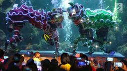 """Pengunjung menyaksikan pertunjukkan barongsai di dalam air di Seaworld Ancol, Jakarta, Minggu (3/2). Pertunjukan dalam rangka memeriahkan Tahun Baru Imlek 2570 tersebut mengangkat tema """"The Legend of 12 Shio"""". (Liputan6.com/Johan Tallo)"""