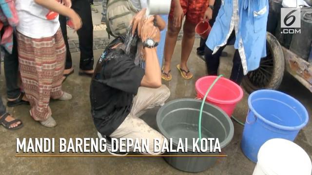 Kesulitan akses air bersih yang dirasakan warga Jakarta Utara membuat mereka berdemo di depan Balai Kota sambil mandi.