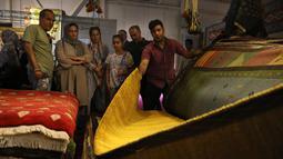 Pedagang memamerkan karpet tenun dagangannya kepada pengunjung pameran di Teheran, Iran, Kamis (29/8/2019). Selama ini AS merupakan pasar karpet Iran terbesar di dunia. (AP Photo/Vahid Salemi)
