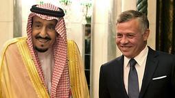 Raja Yordania Abdullah II (kanan) serta Raja Arab Saudi Salman bin Abdulaziz di Mekah, Arab Saudi, Senin (11/6). Arab Saudi bersama Kuwait dan UEA membahas krisis ekonomi Yordania. (Yousef Allan/Saudi Royal Palace/AFP)