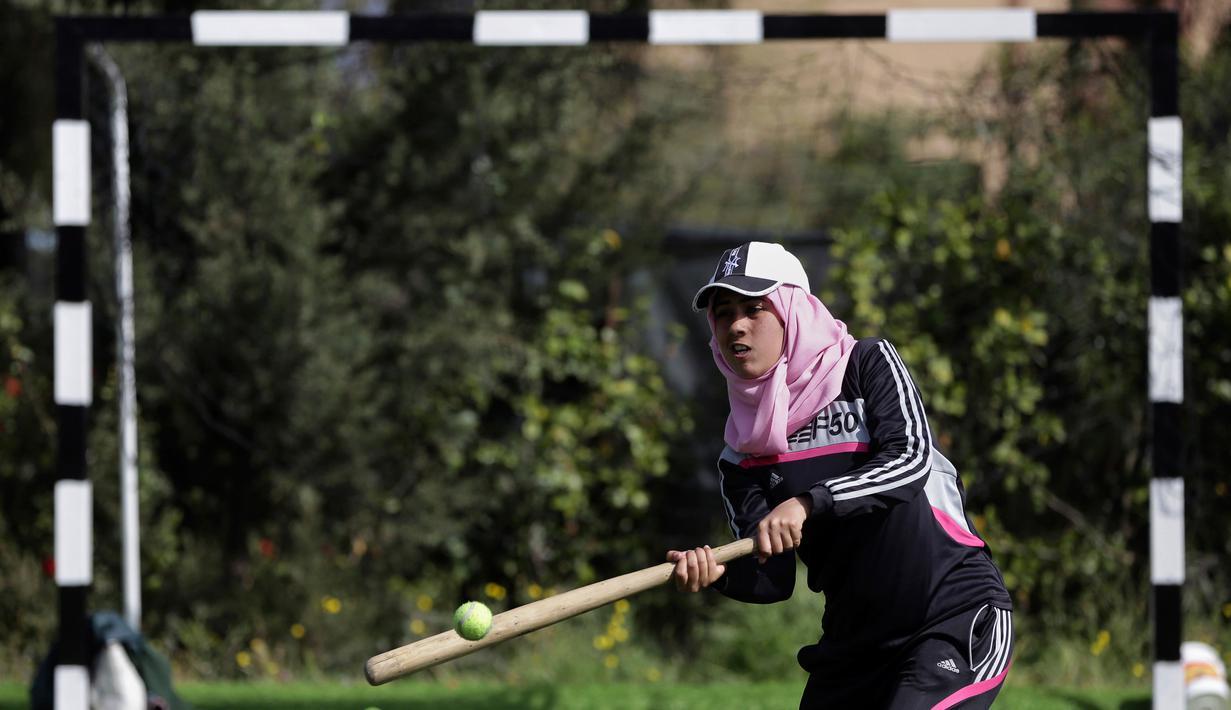 Seorang wanita Palestina memukul bola saat mengikuti sesi latihan bisbol di Khan Younis, Jalur Gaza, 19 Maret 2017. Sekelompok wanita muda muslim mencoba olahraga bisbol sebagai hiburan. (AP Photo/Khalil Hamra)