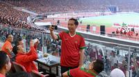 Presiden Joko Widodo (Jokowi) tampak asyik membuat vlog dengan kamera handphone saat menyaksikan laga final Piala Presiden 2018 antara Persija Jakarta vs Bali United di Stadion Utama Gelora Bung Karno, Sabtu (17/2). (Liputan6.com/Pool/Biro Pers Setpres)