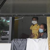 Pasien Covid-19 bersama seorang anak terlihat dari jendela Graha Wisata Ragunan, Jakarta, Selasa (15/6/2021). Pemprov DKI memfungsikan kembali Graha Wisata Ragunan sebagai tempat isolasi warga terpapar COVID-19 kategori OTG sejak pekan lalu dan saat ini merawat 117 pasien. (merdeka.com/Arie Basuki)