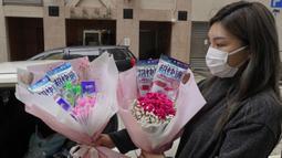Pemilik toko bunga Iris Leung memberikan bunga dengan masker kepada pembeli pada Hari Valentine di Hong Kong, Jumat (14/2/2020). China  melaporkan peningkatan tajam dalam jumlah orang yang terinfeksi virus baru, ketika jumlah korban mendekati 1.400. (AP Photo/Vincent Yu)