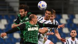 Striker Juventus, Cristiano Ronaldo (kanan) berduel udara dengan bek Sassuolo, Vlad Chiriches dalam laga lanjutan Liga Italia 2020/2021 pekan ke-36 di Mapei-Citta del Tricolore Stadium, Rabu (12/5/2021). Juventus menang 3-1 atas Sassuolo. (AFP/Marco Bertorello)