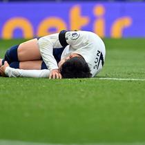 Winger Tottenham Hotspur Son Heung-min (kiri) kesakitan usai berbenturan dengan kiper Chelsea Kepa Arrizabalaga pada laga Liga Inggris, Minggu (19/9/2021). (AFP/Justin Tallis)