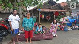 Keluarga Pak Piat berpose di depan kediamannya Desa Sumber Urip Pebayuran, Kabupaten Bekasi, Jawa Barat, Senin (22/2/2021). Banjir merenda keluarga tersebut merapikan barang-barang dan bersihkan rumah yang sudah surut. (Liputan6.com/Herman Zakharia)