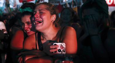 Aktivis hak-hak aborsi menangis setelah anggota parlemen menyetujui undang-undang yang melegalkan aborsi di luar Kongres, Buenos Aires, Argentina, Rabu (30/12/2020). Kongres Argentina menyetujui undang-undang yang melegalkan aborsi. (AP Photo/Natacha Pisarenko)