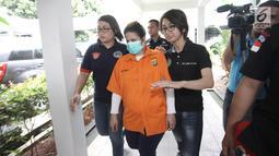 Dhawiya Zaida dikawal petugas saat dihadirkan dalam rilis di Polda Metro Jaya, Jakarta, Sabtu (17/2). Mereka diamankan petugas saat melakukan pesta narkoba di rumahnya dikawasan Cawang. (Liputan6.com/Arya Manggala)