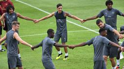 Gelandang Arsenal, Mesut Ozil (tengah) menjalani sesi latihan untuk kompetisi pramusim International Champions Cup (ICC) 2018 di Singapura, Rabu (27/5). Menjelang duel kontra Atletico Madrid, Ozil dkk menikmati sesi latihan ringan. (AFP/Roslan RAHMAN)