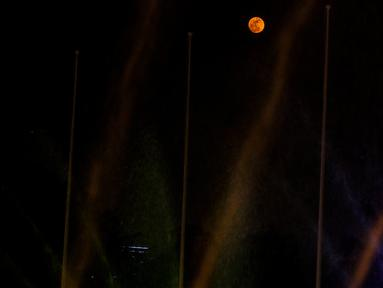 Penampakan bulan purnama di tengah air mancur yang menghiasi lanagit kawasan Jakarta, Jumat (13/9/2019). Malam hari ini, masyarakat bisa melihat bulan purnama yang dinamai Harvest Moon karena bulan mencapai kecerahan puncak dekat dengan titik balik musim semi. (Liputan6.com/Johan Tallo)
