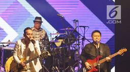 Aksi panggung Jikustik bersama mantan vokalisnya, Pongki Barata (kiri) dalam konser bertajuk 'Jikustik Reunian' di Grand Pasific Hall, Yogyakarta, Jumat (29/3). Ribuan penonton tak malu mengeluarkan suara mereka dan bernyanyi bersama. (Fimela.com/Bambang E. Ros)