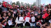 Ketua Nasional Relawan Tim Alpha Jokowi-Ma'ruf Amin, Rieke Diah Pitaloka (tengah) bersama pekerja migran menunjukkan surat deklarasi Tim Zona Alpha Hongkong mendukung pasangan Jokowi-Ma'aruf Amin di Hongkong, Minggu (23/9). (Liputan6.com/HO/Tim Alpha)