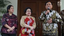 Ketua Umum Partai Gerindra, Prabowo Subianto (kanan) bersama Ketua Umum PDIP, Megawati Soekarnoputri (tengah) memberi keterangan terkait pertemuan dan makan siang bersama di kediaman Megawati di Jalan Teuku Umar, Jakarta, Rabu (24/7/2019). (Liputan6.com/Helmi Fithriansyah)