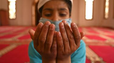 Seorang anak yatim Muslim mengenakan masker berdoa sambil menjaga jarak sosial di dalam pusat panti asuhan selama bulan suci Ramadan di Srinagar (11/5/2020). (AFP/Tauseff Mustafa)