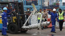 Petugas memindahkan salah satu bagian dari roda pesawat Lion Air PK-LQP JT 610 di Pelabuhan JICT 2, Jakarta, Senin (5/11). Bagian tersebut dipindah untuk dilakukan identifikasi dan pengecekan lebih lanjut oleh KNKT. (Liputan6.com/Helmi Fithriansyah)