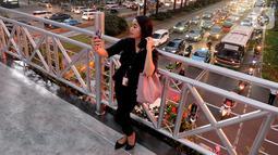 Seorang pejalan kaki berswafoto di jembatan penyeberangan orang (JPO) yang tidak beratap di jalan Sudirman, Jakarta, Rabu (6/11/2019). Pemprov DKI mengklaim mayoritas masyarakat Jakarta setuju dengan konsep JPO terbuka dan tanpa atap yang kini dibangun di Sudirman. (merdeka.com/Arie Basuki)
