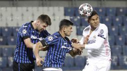 Gelandang Real Madrid, Casemiro (kanan) berebut bola di udara dengan dua pemain Atalanta, Cristian Romero (tengah) dan Berat Djimsiti dalam laga leg pertama babak 16 Besar Liga Champions 2020/21 di Gewiss Stadium, Bergamo, Rabu (24/2/2021). Real Madrid menang 1-0 atas Atalanta. (AP/Luca Bruno)