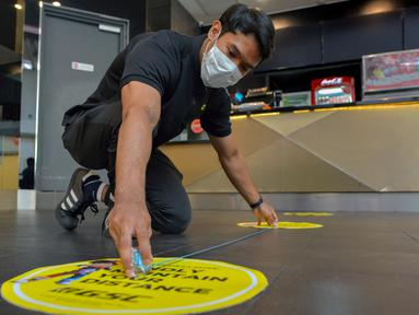 Seorang staf memasang penanda untuk mengingatkan pengunjung menjaga jarak sosial sebagai persiapan pembukaan kembali bioskop di Kuala Lumpur, Malaysia (26/6/2020). Pemerintah Malaysia mengizinkan bioskop dan teater untuk beroperasi kembali mulai 1 Juli mendatang. (Xinhua/Chong Voon Chung)
