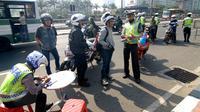Sejumlah pengendara motor terkena tilang di sepanjang Jalan Jendral Sudirman, Jakarta, Sabtu (30/5/2015). Polisi menggelar razia patuh jaya untuk menertibkan para pengendara yang melanggar lalu lintas, mulai 27 Mei-9 Juni. (Liputan6.com/Yoppy Renato)
