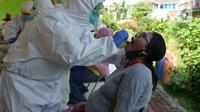 Petugas medis Puskesmas Kecamatan Kramat Jati mengambil sampel lendir saat tes usap (Swab Test) COVID 19 bagi ibu hamil di Jakarta Timur, Jumat (12/6/2020). Tes yang menjadi salah satu syarat untuk menjalani persalinan ini diikuti sekitar 70 ibu hamil. (merdeka.com/Imam Buhori)