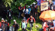 Massa buruh melintasi taman pembatas jalan di sekitar Kawasan Patung Patung Arjuna Wiwaha saat aksi perayaan hari Buruh Internasional 2017 di Jakarta, Senin (5/1). Ribuan massa buruh ikut turun ke jalan. (Liputan6.com/Helmi Fithriansyah)