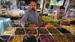 Seorang pedagang menjual zaitun dan acar sayuran di pasar populer di Baghdad, Irak (24/5/2019). Umat Muslim di seluruh dunia tengah melaksanakan puasa dimana mereka tidak makan, minum mulai dari matahari terbit hingga terbenam. (AFP Photo/Ahmad Al-Rubaye)