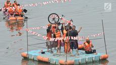 Tim pemenang mengangkat sepeda sebagai hadiah usai menjuarai lomba dayung di Kanal Banjir Timur, Jakarta, Sabtu (17/8/2019). Dalam memeriahkan HUT ke-74 RI, petugas UPK Badan Air DLH Kecamatan Duren Sawit menggelar sejumlah perlombaan, salah satunya lomba dayung. (merdeka.com/ Iqbal S. Nugroho)