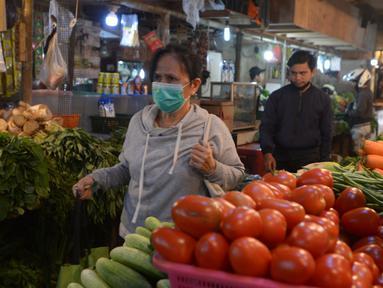 Seorang wanita yang mengenakan masker berjalan di Pasar Senen, Jakarta, Kamis (22/10/2020). Pedagang mengeluhkan sepinya pembeli karena terdampak pandemi COVID-19 serta ramainya demo Omnibus Law UU Cipta Kerja beberapa minggu ini. (merdeka.com/Imam Buhori)