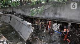 Petugas PPSU melintasi tembok jebol akibat derasnya arus banjir rob di Kompleks Perumahan Pantai Mutiara, Pluit, Jakarta, Minggu (7/6/2020). (merdeka.com/Iqbal S. Nugroho)