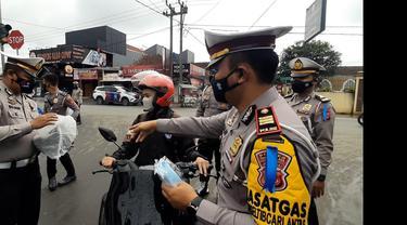 Petugas Polres Tasikmalaya, tengah memberikan reward helm bagi pengguna roda yang patuh menggunakan masker dan bersurat kendaraan lengkap, namun tidak berhelm, saat hari pertama operasi lodaya 2021.