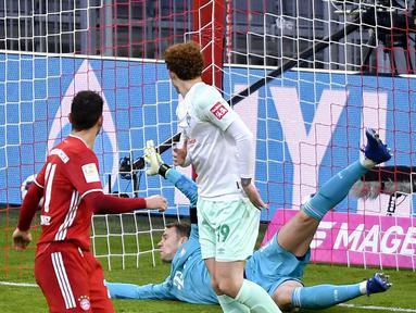 Kiper Bayern Munich, Manuel Neuer, berhasil menepis tendangan pemain Werder Bremen dalam laga lanjutan Liga Jerman pekan ke-8 di Allianz Arena, Sabtu (21/11/2020). Bayern bermain imbang 1-1 dengan Werder Bremen. (AFP/Lukas Barth/Pool)