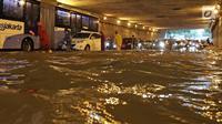 Petugas mengatur arus lalu lintas saat banjir melanda underpass Cawang, Jalan MT Haryono, Jakarta, Selasa (12/12). Hujan deras dan buruknya drainase di kawasan ini menjadi penyebab utama adanya genangan air hingga 50 cm. (Liputan6.com/Herman Zakharia)