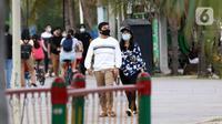 Pengunjung berpasangan menikmati suasana pantai di Taman Impian Jaya Ancol, Jakarta, Kamis (29/10/2020). Libur panjang di masa pemberlakuan PSBB transisi Jakarta dimanfaatkan warga untuk mengunjungi lokasi-lokasi wiisata. (Liputan6.com/Helmi Fithriansyah)