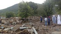 Warga memeriksa kerusakan usai banjir bandang di Desa Ile Ape, Pulau Lembata, Nusa Tenggara Timur, Selasa (6/4/2021). Tim penyelamat terus menggali puing tanah longsor untuk mencari korban yang terkubur usai bencana banjir bandang. (AP Photo/Ricko Wawo)